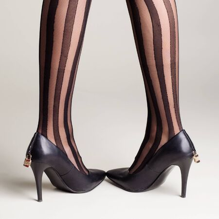 Woman in striped tights black high heel shoes with a padlock posing on a gray background. - image