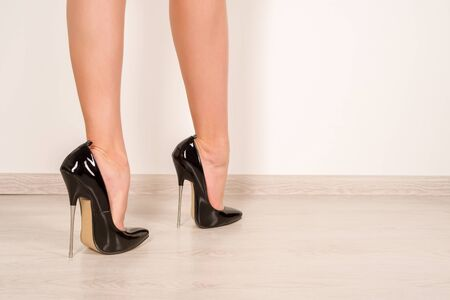 Woman legs in black shiny patent leather stiletto high heels with ankle strap - image