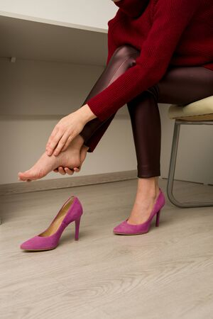 Woman suffering from leg pain in office. She rubbed terrible calluses from uncomfortable high-heeled shoes Reklamní fotografie - 140315109