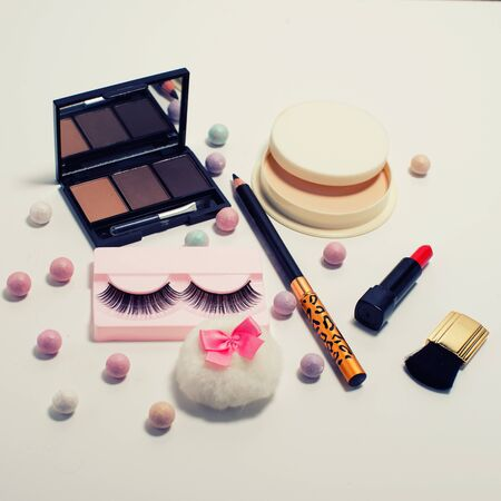 Set of decorative cosmetics false eyelashes, powder, lipstick ,eye shadow white background. Top view of essentials for modern young woman. Reklamní fotografie