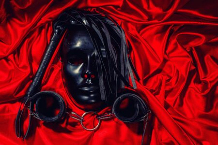 Bondage, kinky adult sex games, kink and BDSM lifestyle concept with a mask, pair of leather handcuffs, flogger, ball gag and a coller with a leash attached on red silk . toned Stock Photo