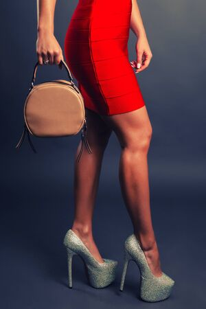 Celebration evening fashion concept. Woman in red short dress red spiked shoes holding handbag, female legs in high heels