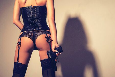 female of young woman or girl in panties and leather corset with a pistol in hand. demon shadow on the wall