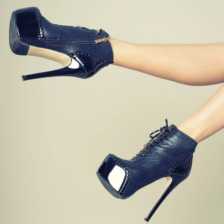 Perfect female legs wearing high heels isolated on gray background.