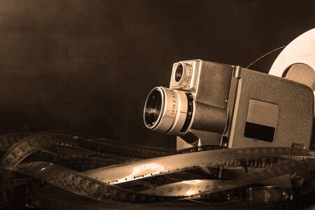 8 mm movie camera with a reel of film in smoke. dark background. black and white
