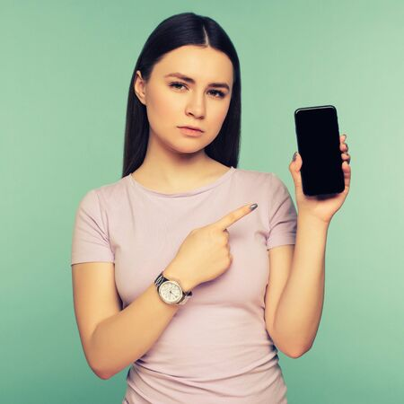 Young sad girl points at smartphone on blue background. The concept of Internet dependence on social networks