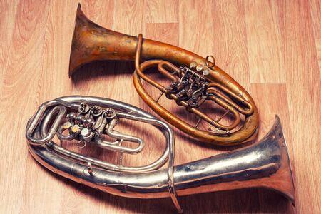 two old rusty alto saxhorn on wooden background. Archivio Fotografico