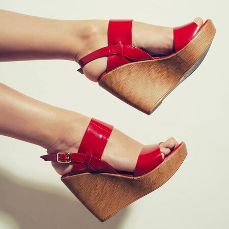 Beautiful female legs in red sandals on a wedge.