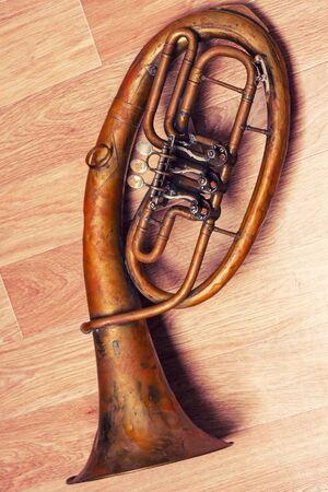 old rusty alto saxhorn on wooden background. Archivio Fotografico