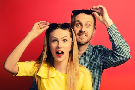 Wow. Surprised man and woman in glasses with open mouth an embrace on a red background Stock Photo