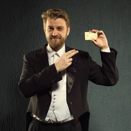 Positive man in a tailcoat pointing finger to the credit card. Stock Photo