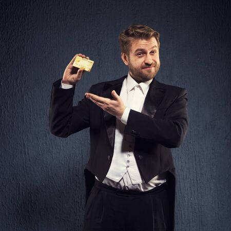 Positive man in a tailcoat demonstrates shows a credit card.