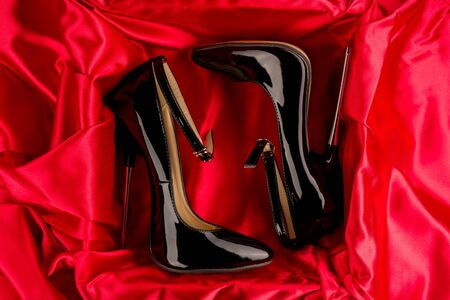 Black shiny patent leather stiletto high heels with ankle strap on red satin background