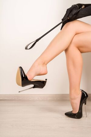 Woman with whip in black fetish shiny patent leather stiletto high heels with ankle strap - image