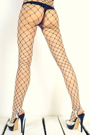 Seductive woman's legs wearing fishnet stockings and high heels standing sideway on white wooden pallets