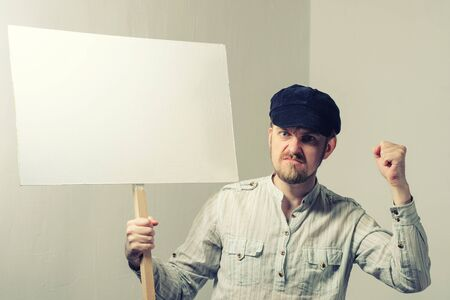 Angry protesting worker with blank protest sign. Imagens