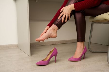 Woman suffering from leg pain in office. She rubbed terrible calluses from uncomfortable high-heeled shoes