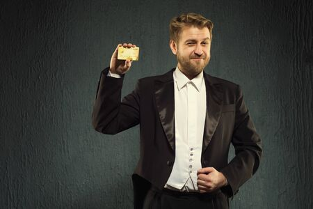 Positive man in a tailcoat offers a credit card. - image Stock Photo