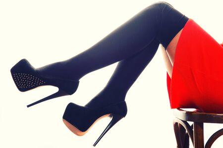 Slim female legs in dark stockings wearing high heels over.