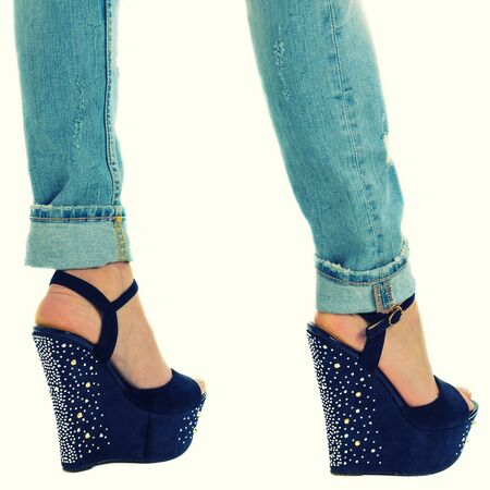 girl in jeans and high heels with studs and rhinestones on white background Standard-Bild