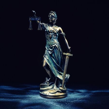 Themis statuette stands on the old vintage stone table. Picture taken with a light brush - Image