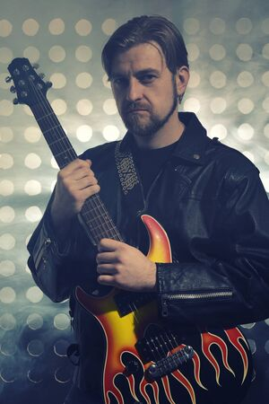 Attractive bearded man with glasses and black leather jackets plays guitar in smoke Stockfoto