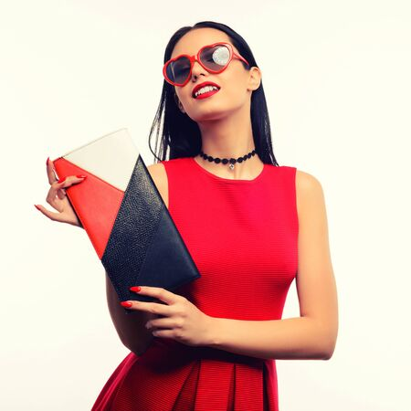 An attractive girl in a red dress and wearing sunglasses in the shape of a heart holds a multicolored clutch in her hands