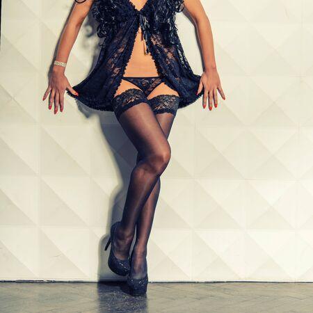 Beautiful woman legs in white stockings on high heels standing on windowsill Stockfoto