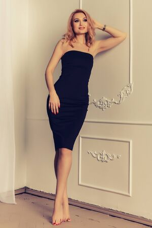 Attractive woman with long blonde hair dressed in fashionable black midi dress with short. Laughing female model standing against white wall on background.