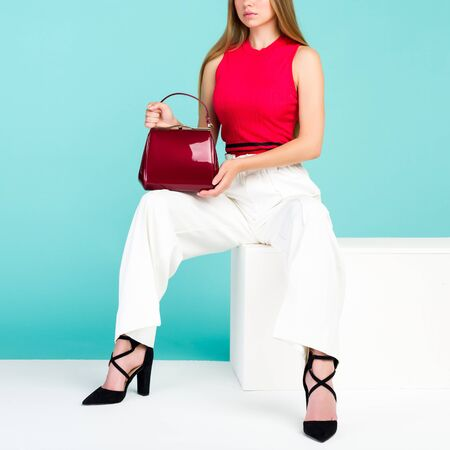 Beautiful woman sitting on the bench with red handbag purse and high heel shoes. - image