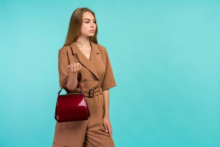 Young fashion woman hold handbag clutch isolated on blue background - image