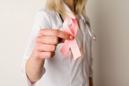 Woman doctor holding a pink ribbon in her hands - image