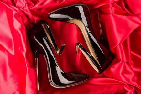 Black fetish shiny patent leather stiletto high heels with ankle strap on red satin background