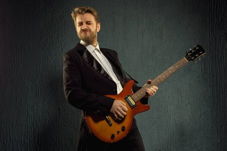 Guitar player with beard and black tailcoat emotionally plays music