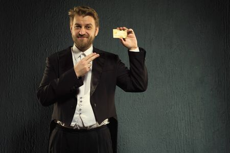 Positive man in a tailcoat pointing finger to the credit card. - image