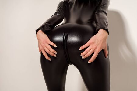 Adult sex games. Submissive girl in spandex catsuit holding her buttocks. spanking. bdsm theme. - image