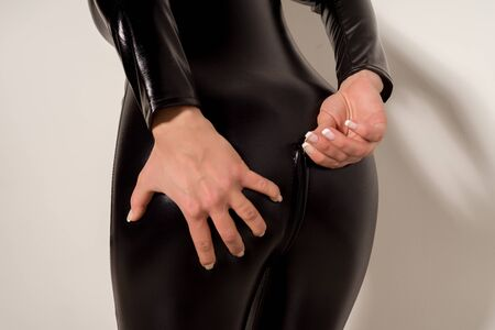 Adult sex games. Submissive girl in spandex catsuit unzips the ass. - image