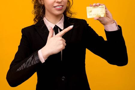 Portrait of a beautiful young business woman standing isolated over yellow background, holding credit card - image Stockfoto
