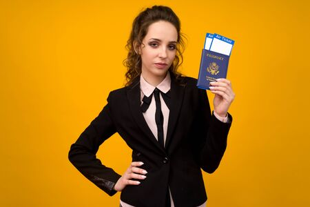 Business Woman Holding Tickets And Passport On Yellow Studio Background - image
