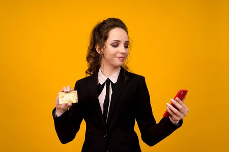 Photo of pleased young woman posing isolated over yellow wall background using mobile phone holding debit card. - image Stockfoto