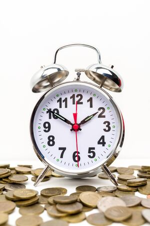 Retro alarm clock and coins . Retirement planning. money saving and Investment. White background