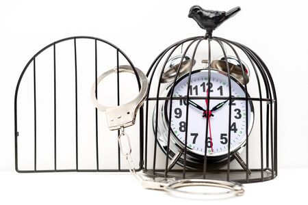 Closed handcuffs hang on the bird cage with alarm clock. Concept of imprisonment