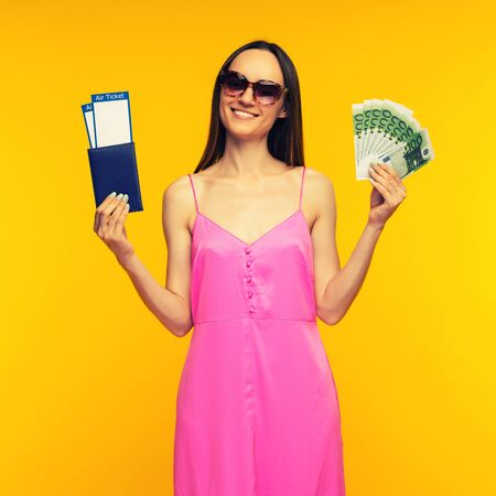 Slender girl in a pink dress and sunglasses holding passport with air ticket and hundred euro bills on a yellow background