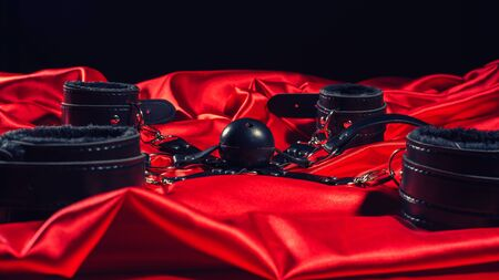 Bdsm outfit. Bondage and Gag ball on the red linen. Adult sex games. Kinky lifestyle. - image