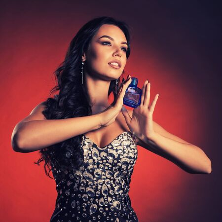 Mysterious beautiful luxurious young woman in a dress with rhinestones posing with perfume in a bottle of blue.