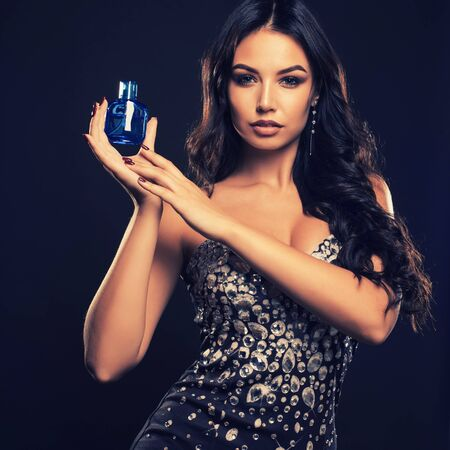 Beautiful young woman with bottle of perfume on dark background Stockfoto