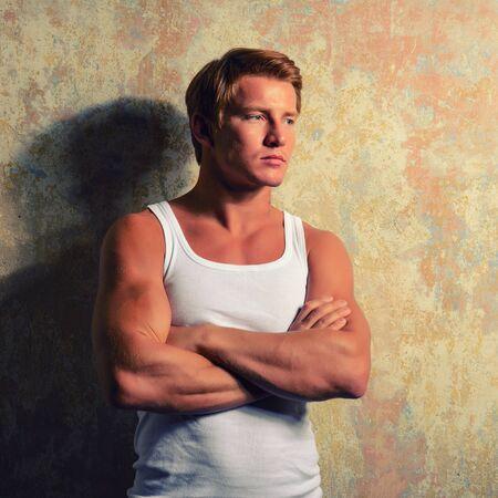 Beautiful  gay in white t-shirt posing against grunge background Stockfoto