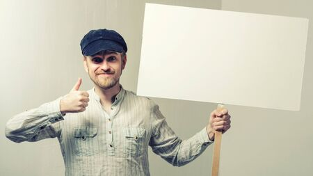 Amazed bearded man showing thumb up and leaning at copy space while standing against white background Stockfoto