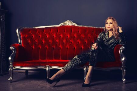 Beautiful young woman in a velor suit sits on a red vintage couch.