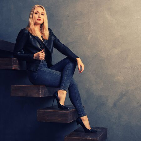 Beautiful woman in a black leather jacket and jeans, heels sitting on a wooden cantilever ladder. Personal growth concept Stockfoto
